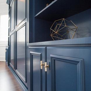 Ejemplo de armario y vestidor unisex y abovedado, clásico renovado, de tamaño medio, con armarios con paneles empotrados, puertas de armario azules, suelo laminado y suelo marrón