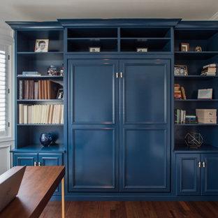 На фото: встроенный шкаф среднего размера, унисекс в стиле современная классика с фасадами с утопленной филенкой, синими фасадами, полом из ламината и коричневым полом с