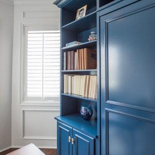 Diseño de armario y vestidor unisex, clásico renovado, de tamaño medio, con armarios con paneles empotrados, puertas de armario azules, suelo laminado y suelo marrón