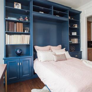 Cette photo montre une armoire encastrée chic de taille moyenne et neutre avec un placard avec porte à panneau encastré, des portes de placard bleues, sol en stratifié et un sol marron.