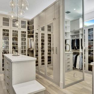マイアミの広い男女兼用コンテンポラリースタイルのおしゃれなウォークインクローゼット (ガラス扉のキャビネット、グレーのキャビネット、淡色無垢フローリング、ベージュの床) の写真