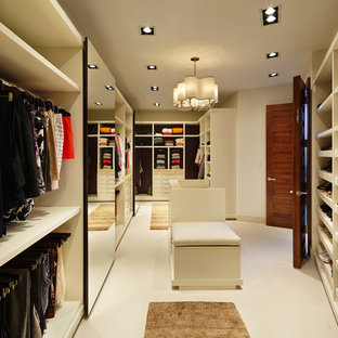 Expansive contemporary walk-in wardrobe in Miami with limestone floors.