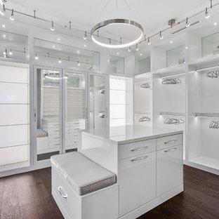 マイアミの広い男女兼用モダンスタイルのおしゃれなフィッティングルーム (フラットパネル扉のキャビネット、白いキャビネット、無垢フローリング、茶色い床) の写真