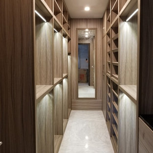 This is an example of a large transitional gender-neutral walk-in wardrobe in Miami with open cabinets, light wood cabinets, marble floors and white floor.