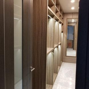 Cette image montre un grand dressing traditionnel neutre avec un placard sans porte, des portes de placard en bois clair, un sol en marbre et un sol blanc.