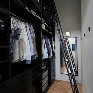 Imagen de armario vestidor de hombre, actual, con puertas de armario negras, suelo de madera clara y suelo beige