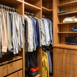 Aménagement d'un dressing room moderne de taille moyenne et neutre avec un placard à porte plane, des portes de placard en bois brun et un sol en bois foncé.