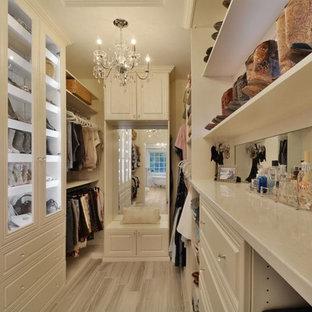 Idee per una grande cabina armadio per donna classica con ante con bugna sagomata e pavimento con piastrelle in ceramica