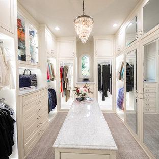 Klassisk inredning av ett stort walk-in-closet för kvinnor, med luckor med profilerade fronter, vita skåp, heltäckningsmatta och beiget golv