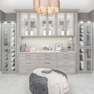 Ispirazione per una grande cabina armadio unisex design con ante di vetro, ante grigie, pavimento in marmo e pavimento beige