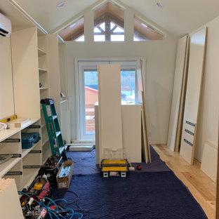 Foto di una cabina armadio unisex chic di medie dimensioni con ante in stile shaker, ante beige, pavimento in legno massello medio e pavimento giallo