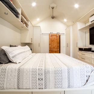 Immagine di una cabina armadio unisex classica di medie dimensioni con ante in stile shaker, ante beige, pavimento in legno massello medio e pavimento giallo