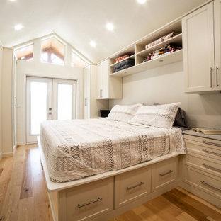 Cette photo montre un dressing chic de taille moyenne et neutre avec un placard à porte shaker, des portes de placard beiges, un sol en bois brun et un sol jaune.