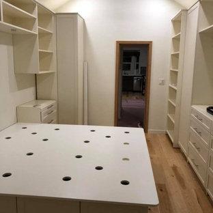 Ispirazione per una cabina armadio unisex chic di medie dimensioni con ante in stile shaker, ante beige, pavimento in legno massello medio e pavimento giallo