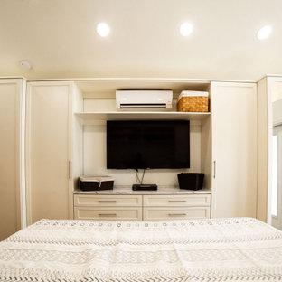 Esempio di una cabina armadio unisex tradizionale di medie dimensioni con ante in stile shaker, ante beige, pavimento in legno massello medio e pavimento giallo