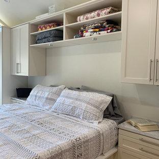 Foto di una cabina armadio unisex classica di medie dimensioni con ante in stile shaker, ante beige, pavimento in legno massello medio e pavimento giallo