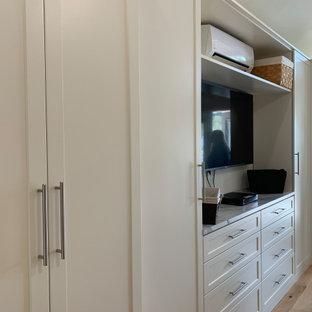 Ispirazione per una cabina armadio unisex tradizionale di medie dimensioni con ante in stile shaker, ante beige, pavimento in legno massello medio e pavimento giallo
