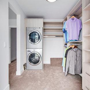 Exempel på ett mellanstort modernt walk-in-closet för könsneutrala, med släta luckor, skåp i ljust trä och heltäckningsmatta