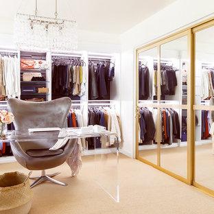 Großes Retro Ankleidezimmer mit Ankleidebereich, offenen Schränken, weißen Schränken, Teppichboden und beigem Boden in Houston