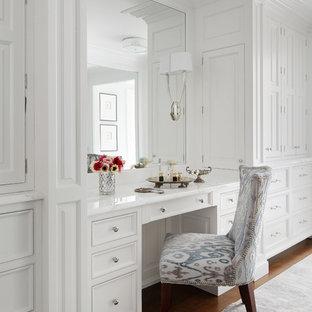 Réalisation d'un grand dressing room tradition pour une femme avec un placard à porte affleurante, des portes de placard blanches et un sol en bois foncé.