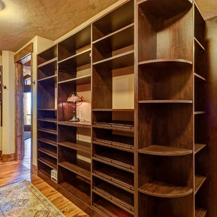 This is an example of a large country gender-neutral walk-in wardrobe in Denver with open cabinets, dark wood cabinets, medium hardwood floors and brown floor.