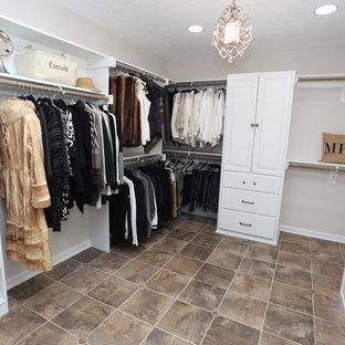 インディアナポリスの中くらいの男女兼用シャビーシック調のおしゃれなウォークインクローゼット (レイズドパネル扉のキャビネット、白いキャビネット、スレートの床、茶色い床) の写真