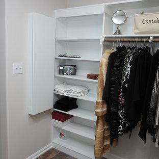 Imagen de armario vestidor unisex, tradicional, de tamaño medio, con armarios con paneles con relieve, puertas de armario blancas, suelo de pizarra y suelo marrón