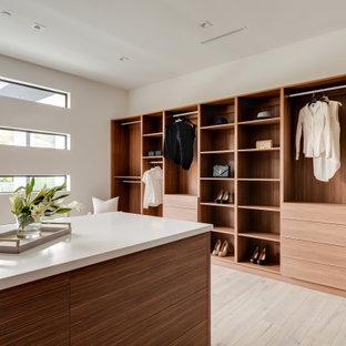 Exempel på ett mycket stort modernt walk-in-closet för könsneutrala, med släta luckor, skåp i mellenmörkt trä, ljust trägolv och brunt golv
