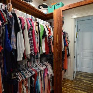 Imagen de armario vestidor de mujer, rústico, grande, con armarios abiertos, puertas de armario con efecto envejecido, suelo de madera oscura y suelo marrón