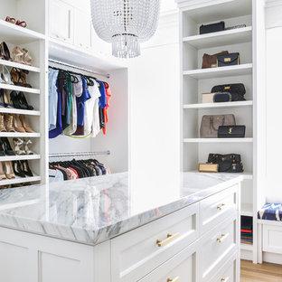 Idées déco pour un grand dressing classique pour une femme avec un placard à porte shaker, des portes de placard blanches, un sol en bois clair et un sol marron.
