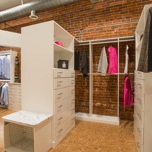 Ejemplo de armario vestidor unisex, actual, de tamaño medio, con armarios con paneles lisos, puertas de armario blancas y suelo de corcho