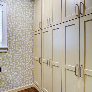 Idée de décoration pour un petit dressing room tradition avec un placard avec porte à panneau encastré, des portes de placard jaunes, un sol en bois foncé et un sol marron.