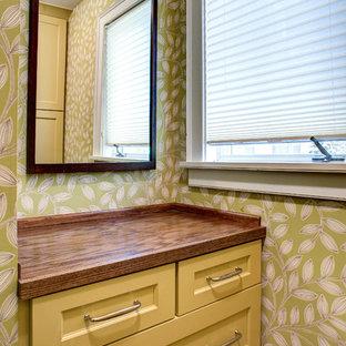 Modelo de vestidor clásico renovado, pequeño, con armarios con paneles empotrados, puertas de armario amarillas, suelo de madera oscura y suelo marrón