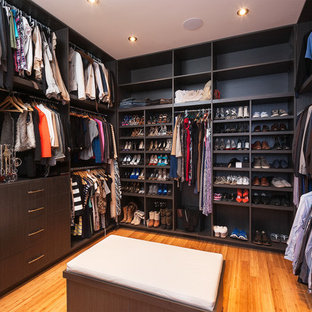Photo of a large modern gender-neutral walk-in wardrobe in Calgary with flat-panel cabinets, dark wood cabinets and bamboo floors.