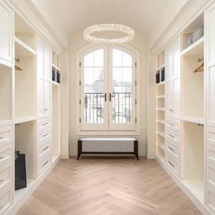 Ejemplo de armario vestidor unisex, tradicional renovado, con armarios con paneles empotrados, puertas de armario blancas y suelo de madera clara