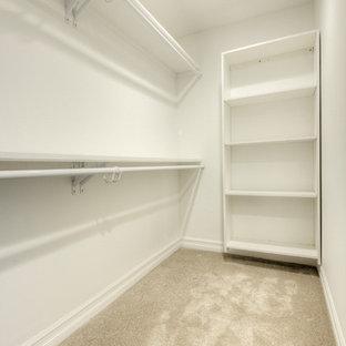 Imagen de armario vestidor de estilo americano, de tamaño medio, con armarios abiertos, puertas de armario blancas, moqueta y suelo gris