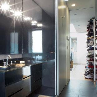 Foto di una cabina armadio per uomo minimalista di medie dimensioni con ante lisce e pavimento nero