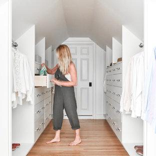 ポートランド(メイン)の男女兼用トランジショナルスタイルのおしゃれなウォークインクローゼット (フラットパネル扉のキャビネット、白いキャビネット、淡色無垢フローリング、ベージュの床) の写真