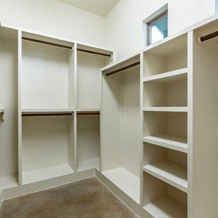 Imagen de armario vestidor unisex, clásico renovado, grande, con armarios abiertos, puertas de armario blancas, suelo de cemento y suelo marrón