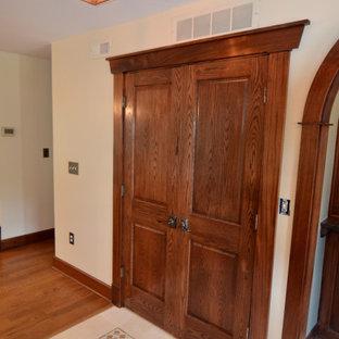 Foto de armario y vestidor de estilo americano con armarios con paneles con relieve, puertas de armario de madera en tonos medios y suelo de mármol