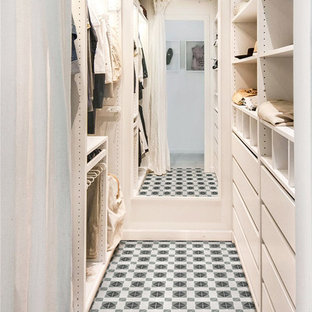 Contemporary gender-neutral walk-in wardrobe in Orange County with porcelain floors, multi-coloured floor, flat-panel cabinets and white cabinets.