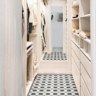 オレンジカウンティの男女兼用コンテンポラリースタイルのおしゃれなウォークインクローゼット (磁器タイルの床、マルチカラーの床、フラットパネル扉のキャビネット、白いキャビネット) の写真