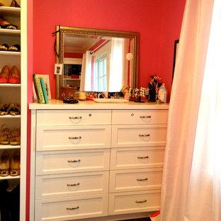 Mittelgroßer Klassischer Begehbarer Kleiderschrank mit weißen Schränken, profilierten Schrankfronten, dunklem Holzboden und braunem Boden in New York