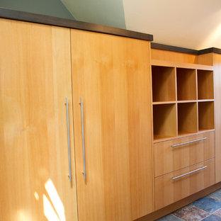 Diseño de armario unisex, bohemio, de tamaño medio, con armarios con paneles lisos, puertas de armario de madera clara y suelo de pizarra