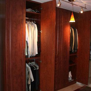 Diseño de armario vestidor de hombre, tradicional, de tamaño medio, con armarios con paneles con relieve, puertas de armario de madera en tonos medios y suelo de baldosas de cerámica