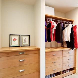Immagine di un grande armadio o armadio a muro unisex moderno con ante lisce, ante in legno chiaro e pavimento in cemento