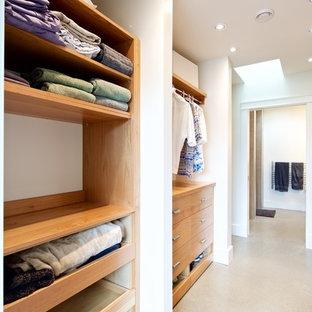 Ejemplo de armario vestidor unisex, moderno, grande, con armarios con paneles lisos, puertas de armario de madera clara y suelo de cemento