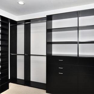 Imagen de armario vestidor clásico, grande, con armarios con paneles lisos, puertas de armario negras, moqueta y suelo beige