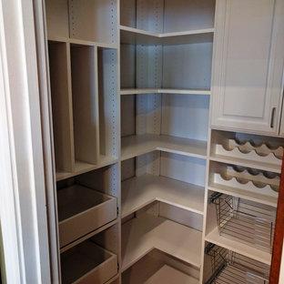 Diseño de armario vestidor unisex, clásico renovado, de tamaño medio, con armarios con paneles con relieve, puertas de armario blancas y suelo de madera en tonos medios