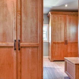 トロントの広い男女兼用トランジショナルスタイルのおしゃれなウォークインクローゼット (シェーカースタイル扉のキャビネット、中間色木目調キャビネット、リノリウムの床) の写真